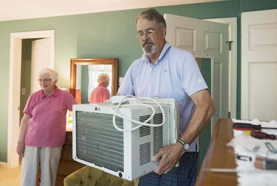 BREWSTER - Nauset Neighbors volunteer Frank Bridges, 66, installs an air conditioning unit for Ann Miller, 79, Tuesday, July 3, 2018. (Christine Hochkeppel for the Boston Globe)